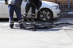 Dois trabalhadores estão nivelando a migalha do asfalto no poço com um arrasto-rolo antes de pavimentar com rolo da construção da fotos de stock royalty free