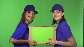 Dois trabalhadores fêmeas alegres do serviço de entrega que sorriem guardando a caixa de cartão filme