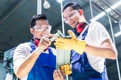Dois trabalhadores industriais que inspecionam a parte do trabalho Imagem de Stock
