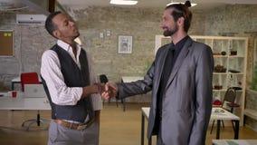 Dois trabalhadores multy-étnicos estão agitando as mãos no escritório, conceito de uma comunicação video estoque