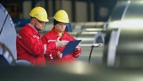 Dois trabalhadores na planta de produção como a equipe que discute, cena industrial no fundo vídeos de arquivo