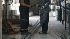 Dois trabalhadores na planta do reforço da fibra de vidro - explore e discuta o projeto na fábrica da indústria pesada video estoque