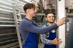 Dois trabalhadores que escolhem o perfil da janela do PVC Imagem de Stock