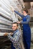 Dois trabalhadores que escolhem o perfil da janela do PVC Imagens de Stock Royalty Free