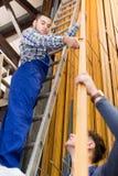 Dois trabalhadores que escolhem o perfil da janela do PVC Fotos de Stock