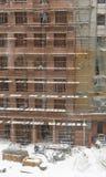Dois trabalhadores que montam o andaime na construção da cidade no mau tempo Imagens de Stock
