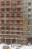 Dois trabalhadores que montam o andaime na construção da cidade no mau tempo Imagem de Stock Royalty Free
