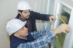 Dois trabalhadores que tomam janelas das medidas foto de stock
