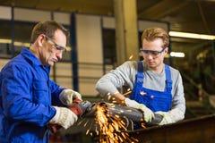 Dois trabalhadores que trabalham com moedor de ângulo Imagens de Stock