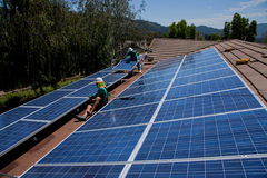 Dois trabalhadores solares masculinos instalam os painéis solares Foto de Stock Royalty Free