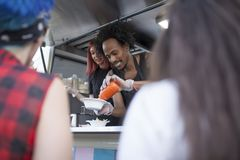 Dois trabalhos dos povos em um caminhão do alimento imagens de stock