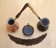 Dois turcos do metal, um copo sobre o café e grãos de café em uma luz Imagem de Stock