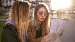 Dois turistas à moda das meninas na roupa ocasional do outono, apreciando suas aventuras na cidade nova Guia do curso, turismo de video estoque