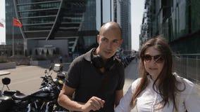 Dois turistas andam através da cidade grande na rua com arranha-céus e com muitas motocicletas estacionadas e apreciam vídeos de arquivo