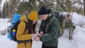 Dois turistas com trouxas, um homem novo e uma menina, em um olhar coberto de neve da floresta do inverno em um mapa de papel vídeos de arquivo