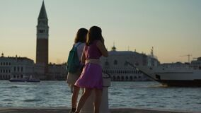 Dois turistas fêmeas que apreciam a ideia da arquitetura da cidade de Veneza, torre de sino do Campanile video estoque