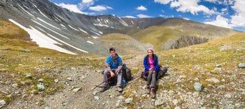 Dois turistas nas montanhas que sorriem no fundo do s imagem de stock