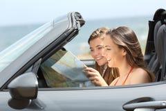 Dois turistas que leem um mapa em um carro convertível fotos de stock royalty free