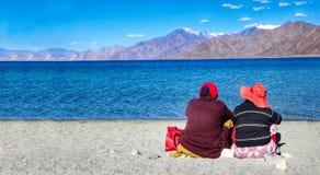 Dois turistas que sentam-se ao lado do lago na solidão durante o dia na frente das águas azuis e das montanhas distantes fotografia de stock