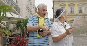 Dois turistas superiores que têm a discussão sobre a rota planejando do turista em Lviv vídeos de arquivo