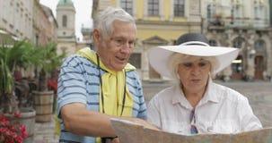 Dois turistas superiores que têm a discussão sobre a rota planejando do turista em Lviv filme