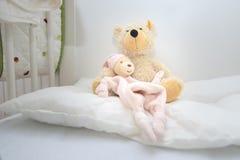 Dois ursos de peluche no cott do bebê que senta-se no descanso branco imagens de stock