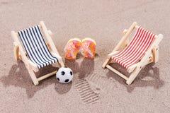 Dois vadios do sol com bola e sapatas na praia Foto de Stock Royalty Free