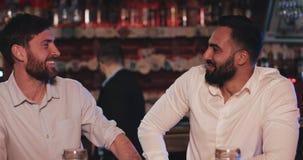 Dois velhos amigos felizes que bebem a cerveja de esboço e que falam na barra de esporte Amigos que sentam-se no contador da barr vídeos de arquivo