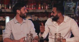 Dois velhos amigos que bebem a cerveja de esboço e que falam na barra de esporte Amigos que sentam-se no contador da barra, cerve vídeos de arquivo