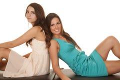Dois vestidos das mulheres sentam as partes traseiras junto Foto de Stock Royalty Free