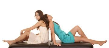 Dois vestidos das mulheres sentam-se de volta à parte traseira Imagens de Stock