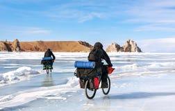 Dois viajantes com as trouxas em bicicletas no gelo do Lago Baikal Foto de Stock Royalty Free