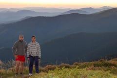 Dois viajantes dos homens sobre uma montanha, uma paisagem bonita do por do sol Fotografia de Stock Royalty Free