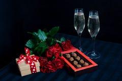 Dois vidros com champanhe e um ramalhete de rosas vermelhas e de doces no fundo preto imagem de stock royalty free