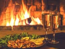 Dois vidros com champanhe e uma placa com camarões, limão e verdes em uma tabela de madeira na perspectiva da imagem de stock