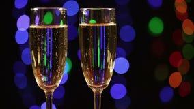 Dois vidros com champanhe sobre o preto video estoque