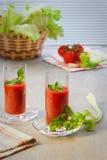 Dois vidros com suco de tomate, tomates, hastes e folhas de um aipo na tabela Foto de Stock Royalty Free