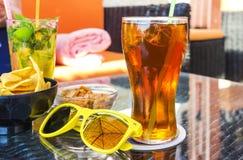 Dois vidros com suco e placa com porcas e microplaquetas, óculos de sol amarelos no primeiro plano em uma tabela no café do ar li imagem de stock