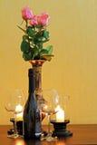 Dois vidros com uma garrafa do vinho na tabela ao lado das velas Imagens de Stock Royalty Free