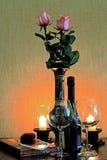 Dois vidros com uma garrafa do vinho na tabela ao lado das velas Foto de Stock Royalty Free