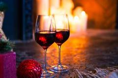 Dois vidros com vinho tinto na árvore de Natal e no backgrou da chaminé Imagens de Stock Royalty Free