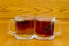 Dois vidros completos com chá e saco dos rooibos no foco macio no fundo de madeira Fotografia de Stock