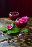 Dois vidros completos da bebida vermelha com bagas, gelo e um flowe cor-de-rosa Fotografia de Stock