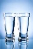 Dois vidros da água em um azul Fotografia de Stock
