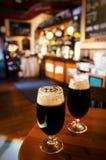 Dois vidros da cerveja escura em uma barra foto de stock royalty free