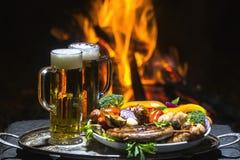 Dois vidros da cerveja no fundo do fogo Foto de Stock Royalty Free