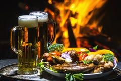 Dois vidros da cerveja no fundo do fogo Fotografia de Stock Royalty Free