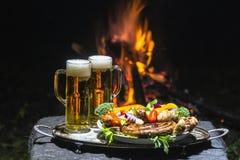 Dois vidros da cerveja no fundo do fogo Imagem de Stock