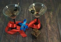 Dois vidros de martini com azeitonas, com escarlate da fita, a orquídea azul e a caixa de presente em uma tabela de madeira foto de stock