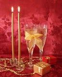 Dois vidros de vinho com champanhe, presentes e velas douradas no vermelho Fotografia de Stock Royalty Free
